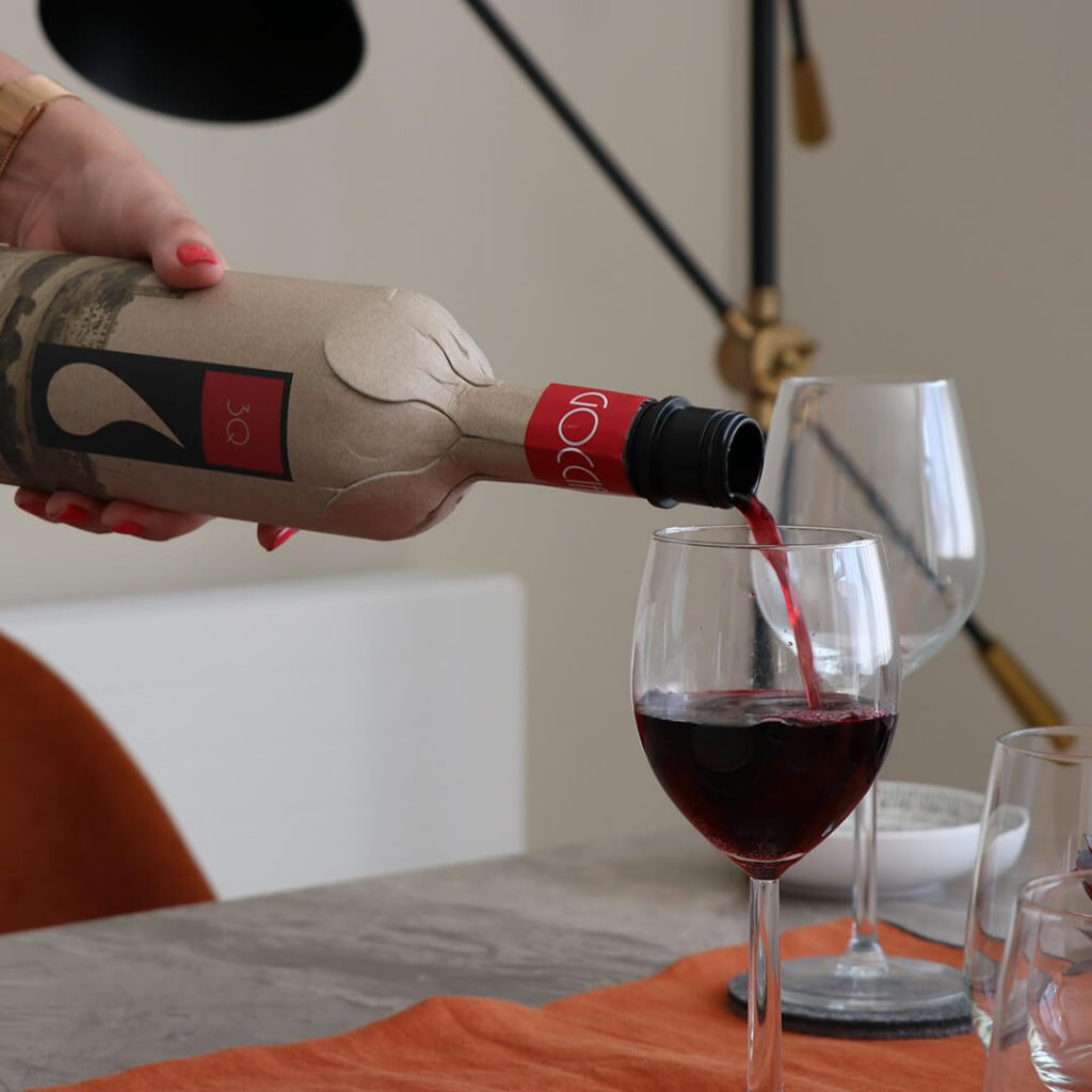 Wine being poured from cardboard wine bottle.